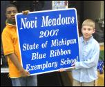 Two students holding up Exemplary School sign