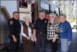 Firefighters posed with community members in front of fire truck