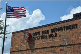 New sign at Fire Station 2 with American flag blowing in the breeze.