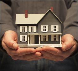 Close up of man holding a replica of a house
