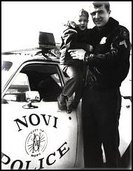 Policeofficer holding child posed in from of Police Car.