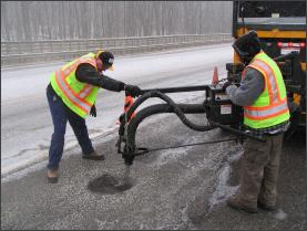 Department of Public Works employees working on pothole