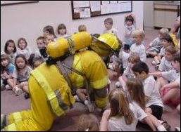 Firefighter in classroom with group of children.